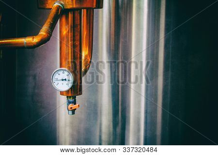 Steam gauge. Industrial equipment for brandy production.  Copper still alembic inside distiller to distill grapes and produce spirits. Noises and large grain - stylization under the film. Soft focus stock photo