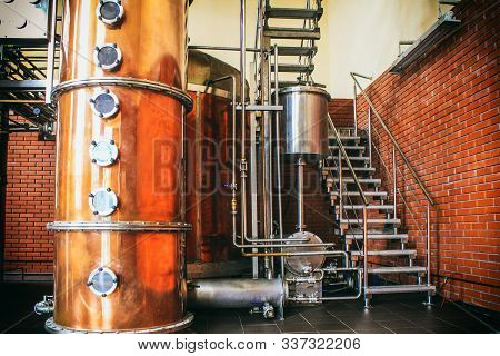 Industrial equipment for brandy production. Copper still alembic inside distiller to distill grapes and produce spirits. Noises and large grain - stylization under the film. Soft focus stock photo