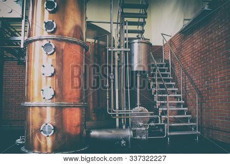 Industrial equipment for brandy production. Copper still alembic inside distiller to distill grapes and produce spirits. stock photo