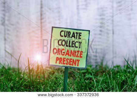 Conceptual hand writing showing Curate Collect Organize Present. Business photo showcasing Pulling out Organization Curation Presenting Plain paper attached to stick and placed in the grassy land. stock photo