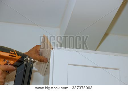 Carpenter nailing crown moldings in the kitchen cabinets framing trim worker using air brad nail gun stock photo