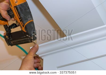 Air nailer tool close up of carpenter using nail gun to crown moldings on kitchen cabinets with white cabinets stock photo