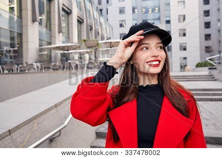 Admirable ravishing luscious girl in red autumn coat and black golf holds her black kepi by hand, looks at side and smiles. Lady stands on the steps near building. stock photo