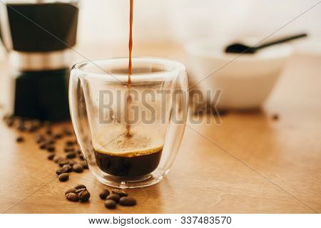 Pouring coffee in glass cup on background of roasted coffee beans, grounded coffee, geyser coffee maker on wooden table. Alternative Coffee brewing concept. Process of making espresso stock photo