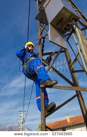 Electrician taking photos on the electric power pole with cell phone stock photo