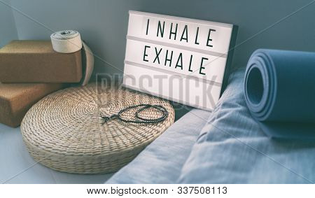 Yoga breathing INHALE EXHALE sign at fitness class on lightbox inspirational message with exercise mat, mala beads, meditation pillow. Accessories for fit home lifestyle. stock photo