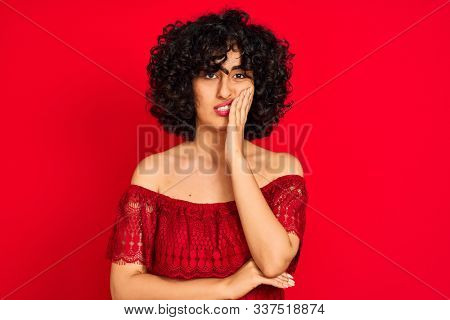 Young arab woman with curly hair wearing casual dress over isolated red background thinking looking tired and bored with depression problems with crossed arms. stock photo