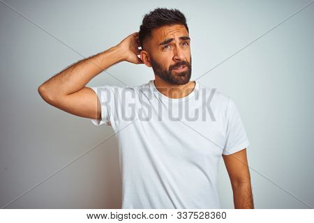 Young indian man wearing t-shirt standing over isolated white background confuse and wondering about question. Uncertain with doubt, thinking with hand on head. Pensive concept. stock photo