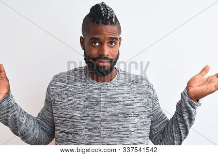 African american man with braids wearing grey sweater over isolated white background clueless and confused expression with arms and hands raised. Doubt concept. stock photo