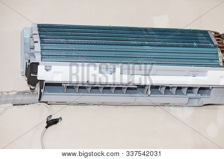 Inverter Air conditioning service, repair and maintenance concept. The specialist cleans and repairs the wall air conditioner. Picture technician cleaning coil cooler of air conditioner stock photo
