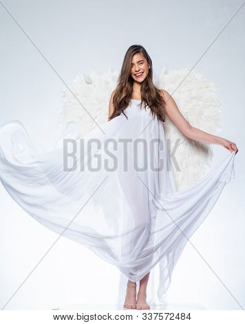Angel woman with feather white wings and gift. Wonderful blonde angel girl with white wings. Art photo of a Angelic beautiful woman stock photo