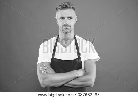 Cooking healthy way. Master of household. Doing household. Home cooking. Grill party. Skilled and confident. Cook wearing bib apron. Bearded mature man in red apron. Mature guy in cooking apron. stock photo