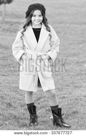 Fancy coat. Classic coat does not have to be boring but sticking to scale of warm, understated tones. Girl fashionable model wear yellow wool coat. Child in warm clothes. Feeling cozy and comfortable. stock photo