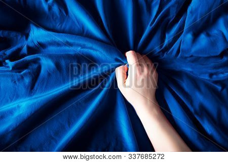 Woman hand on the blue silk bedding, sex and orgasm concept stock photo