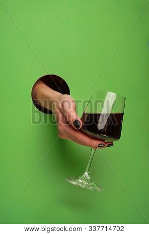 selective focus, a female hand in a round hole, in the background, holding a glass of red wine stock photo