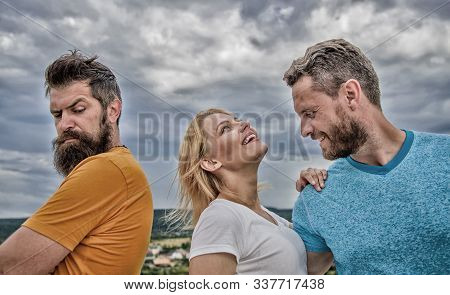 What to do when you feel rejected. Girl stand between two men. Couple and rejected partner. How to get over breakup for guys. Ruined relationships. She made her choice. Woman picked boyfriend stock photo