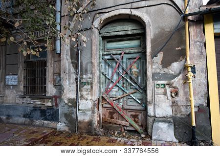 boarded up wooden door with an arch of an old abandoned historic house and a window with bars stock photo