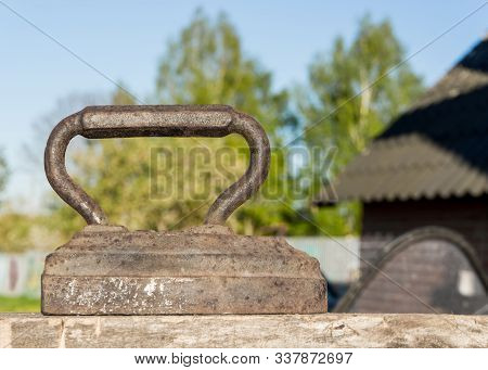 Old Vintage iron for ironing. Antique household item on summer sunny day in village stock photo