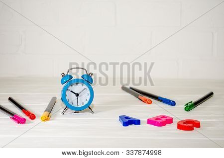 Blue retro alarm clock, ABC letters, colored pens lie on a white background with copyspace. School concept, study, knowledge stock photo