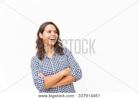 Happy excited female customer staring away at copy space an laughing. Young woman in casual checked shirt standing isolated over white background. Advertising or joy concept stock photo