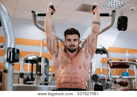 Strong athletic young man bodybuilder fitness model exercise triceps with barbell on the bench in gym stock photo
