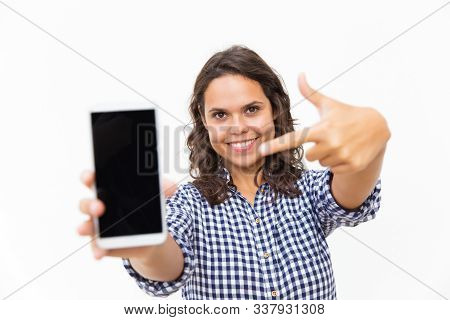 Happy positive customer pointing finger at blank phone screen. Young woman in casual checked shirt standing isolated over white background. Advertising or mobile app concept stock photo