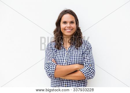Happy joyful student girl with arms folded looking at camera and smiling. Young woman in casual checked shirt standing isolated over white background. Female portrait concept stock photo