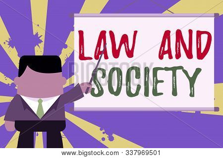 Text sign showing Law And Society. Conceptual photo Address the mutual relationship between law and society Businessman standing in front projector screen pointing project idea. stock photo
