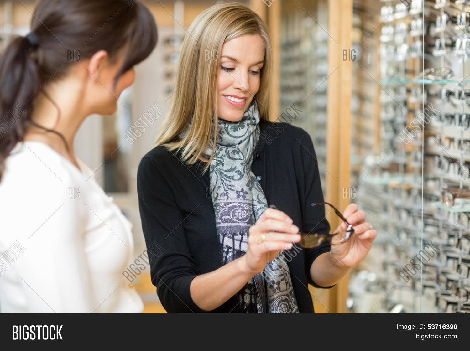 e59244d413 🔥 Young woman examining eyeglasses with salesgirl in optician store