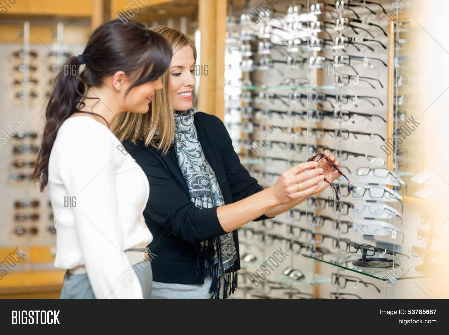 d8c0aa34ad 🔥 Happy woman with salesgirl examining eyeglasses in optician store