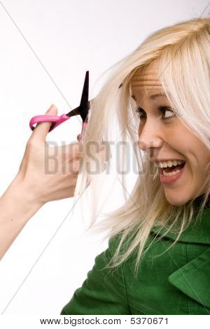 Young blond woman at hairdresser afraid of cutting her hair stock photo