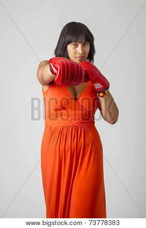 twenty something philipino woman in low cut orange dress throwing a punch with red boxing gloves stock photo