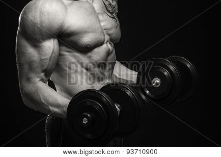 Muscular man bodybuilder with tattoos. Man posing on a black background, shows his muscles. Bodybuilding, posing, black background, muscles - the concept of bodybuilding. Article about bodybuilding. stock photo
