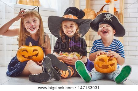 Happy brother and two sisters on Halloween. Funny kids in carnival costumes indoors. Cheerful childr