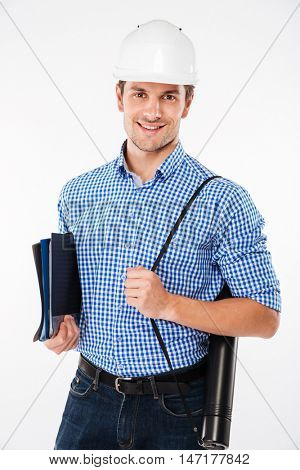 Happy young man building engineer in hard hat holding folders and blueprints stock photo