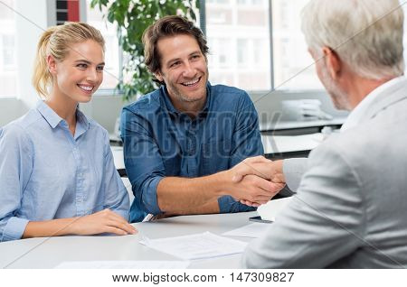 Handshake of a senior financial advisor with a young man and his girlfriend. Businessman handshake with couple during meeting signing agreement. Real estate agent shaking hands with happy couple. stock photo