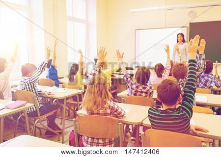 education, elementary school, learning and people concept - group of school kids with teacher sittin