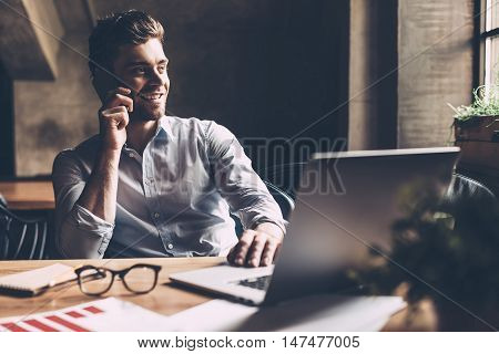 Always in touch with colleagues. Confident young man in smart casual wear talking on the mobile phone and smiling while sitting at his working place in office