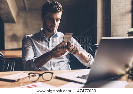 Texting to colleague. Confident young man in smart casual wear holding smart phone and looking at it while sitting at his working place in office