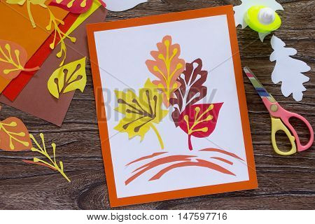 Autumn Leaves Of Colored Paper On A Wooden Background. Sheets Of Paper Crafts For Kids. Children\'s A