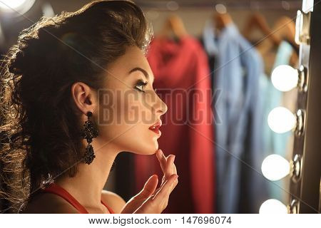 Confident female model is smartening herself up backstage. She is touching her chin gently. Girl is sitting and looking at mirror with serenity stock photo