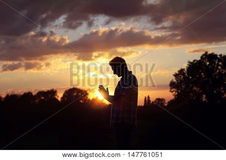 Silhouette of a man praying in the sunset concept for religion, worship, prayer and praise