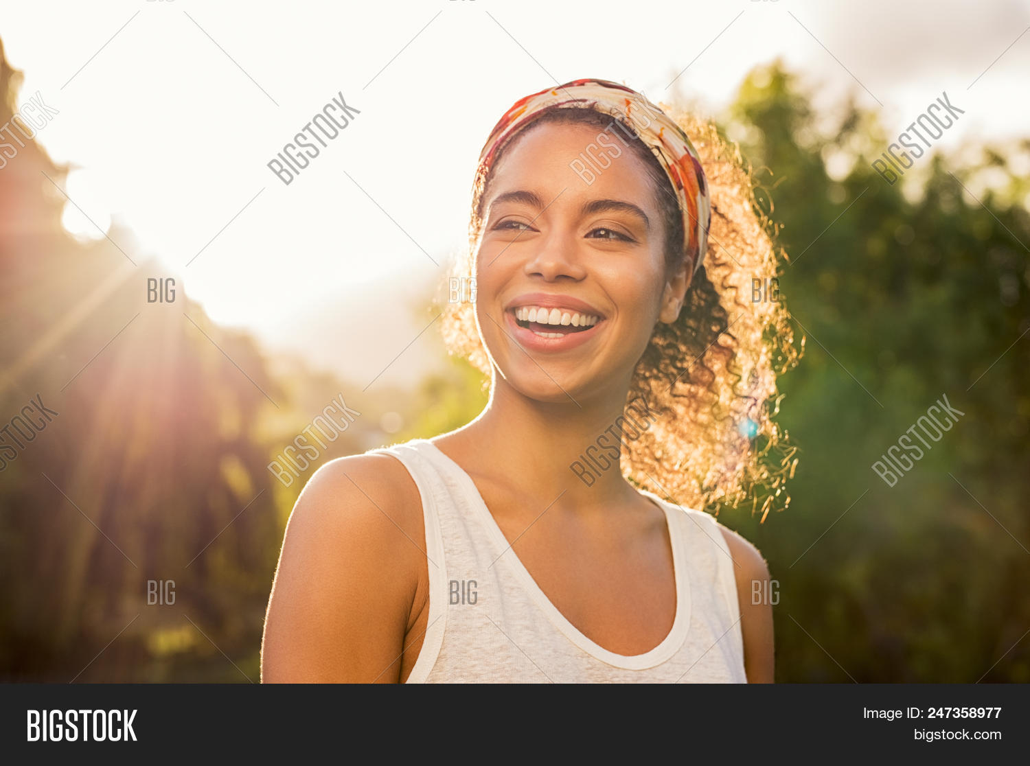 Portrait of beautiful african american woman smiling and looking away at park during sunset. Outdoor
