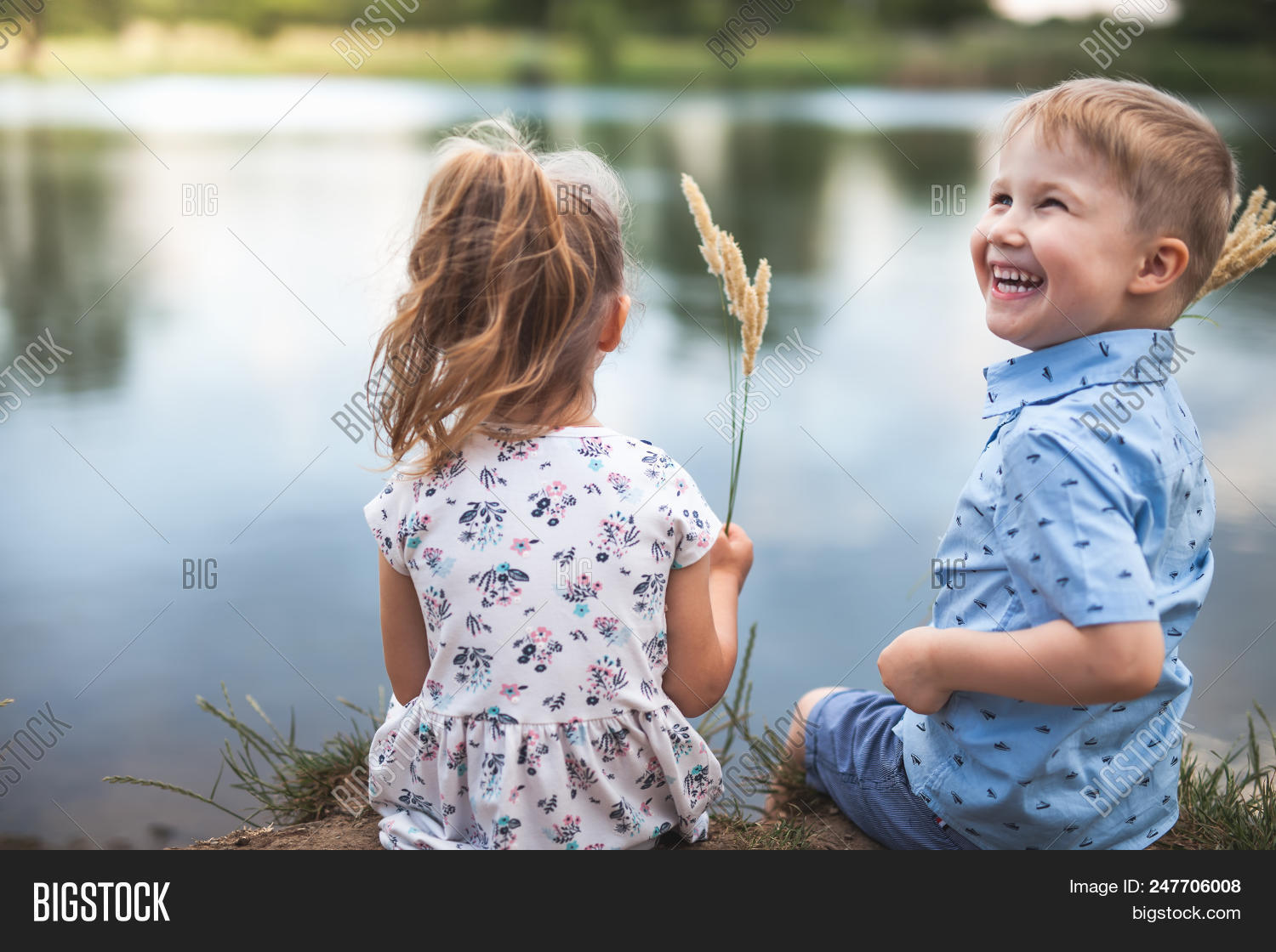 Your Happy Couple Of Kids, Boy Gives Wheat Spikelets Girl. Children Are Sitting Near Lake, Outdoor At Park. Autumn And Summer Season. Happy Family Values. Children's Health Care