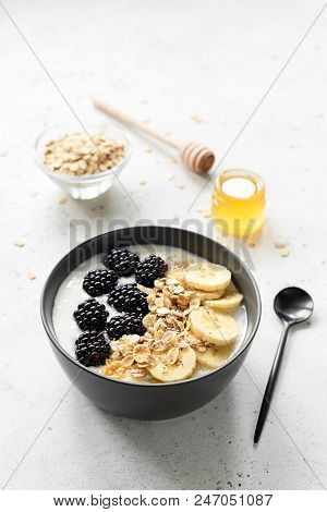 Breakfast smoothie bowl with muesli, blackberries, banana and honey on grey concrete background. Healthy lifestyle, dieting, vegetarian food concept stock photo