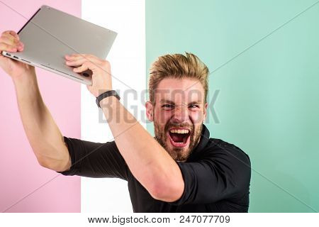 Annoying advertisement promoting brands on internet makes people go crazy angry aggressive. Man laptop annoyed by ads. Internet advertisement. Guy stylish appearance going mad while works laptop. stock photo