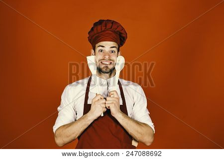 Kitchenware and cooking concept. Chef with excited face holds wooden spoon and spatula near face on red background. Man in cook hat and apron holds cooking tools. Cook works in kitchen. stock photo