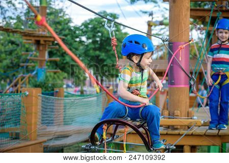Happy children having fun in adventure park. Two adventurous healthy preschool boys, twin brothers enjoying active day outdoors climbing on the trees. Friendship and brotherhood concept. stock photo