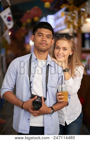Portrait of happy mixed-raced couple with digital camera standing in the street stock photo