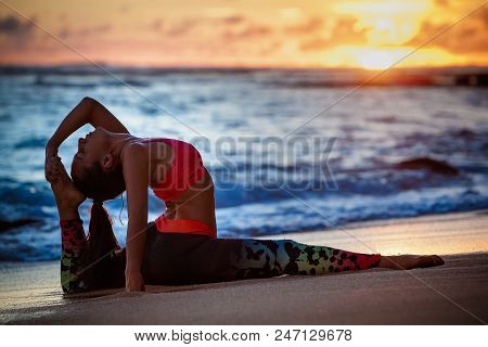 Young active woman stretching in yoga pose on sea beach to keep fit and health. Healthy lifestyle, flexibility training, sport activity in sport camp on summer family holiday. stock photo